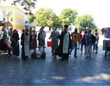Un prêtre orthodoxe répand de l'eau bénite après une Gay Pride