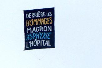 """Pendant la Marseillaise, des ballons et une banderole s'envolent : """"L'économie nous coûte la vie"""" et """"derrière les hommages Macron asphyxie l'hôpital""""."""